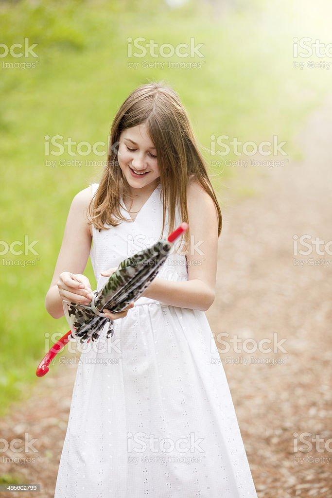 Smiling Girl Closing Umbrella stock photo
