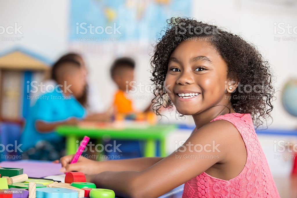 Smiling girl colors in her art class - Photo