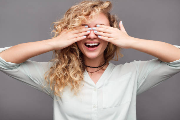 Smiling girl covering eyes with hands stock photo