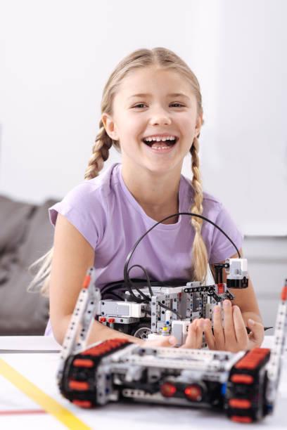 lächelndes mädchen erstellen elektronische roboter in der schule - lernfortschrittskontrolle stock-fotos und bilder
