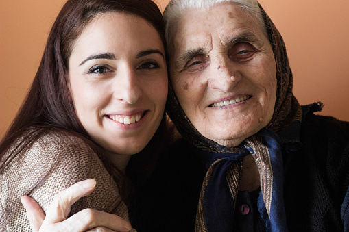 144362548 istock photo Smiling girl embracing her lovely grandmother 636399580
