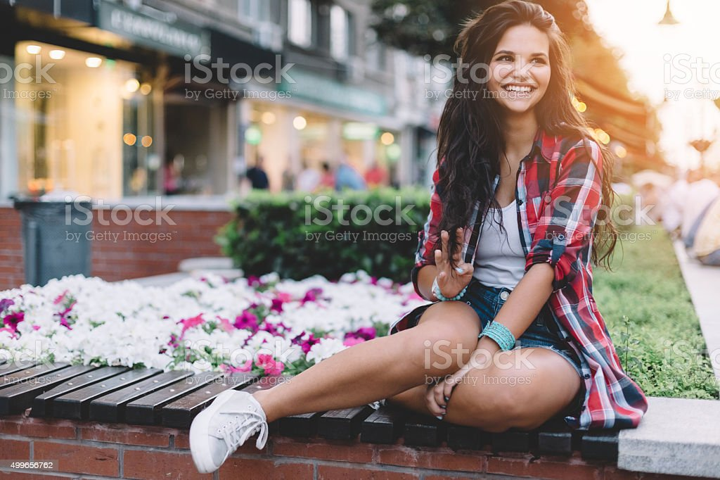 Smiling girl gesturing with hand to say hello stock photo
