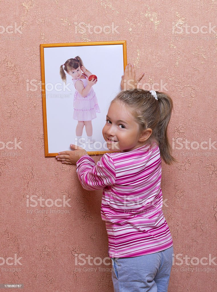 Smiling girl hanging up a self portrait stock photo