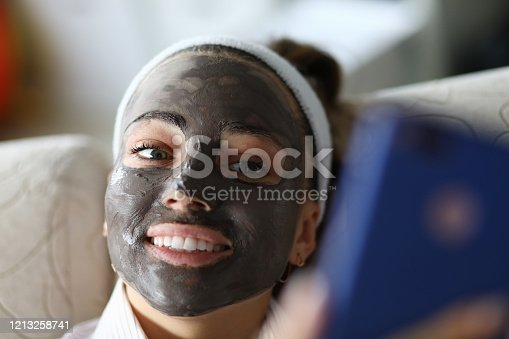 Smiling girl has black coal mask on her face. Moisturizing and soothing for quick recovery. Stimulate blood circulation, smooth surface and skin tone. Innovative high-tech ingredients