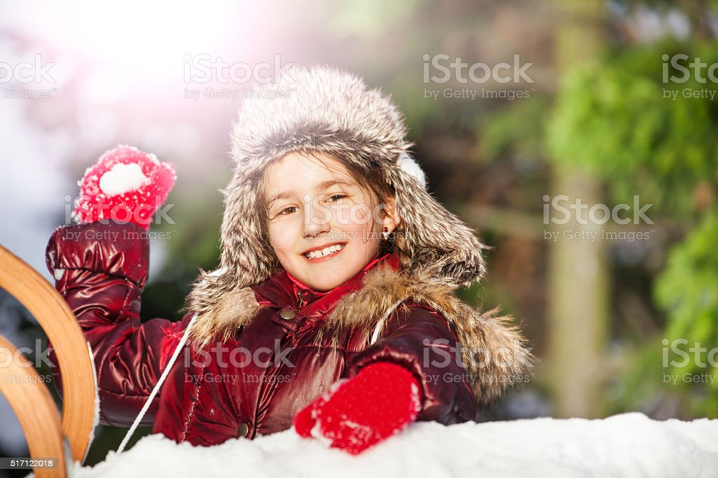 Smiling girl having fun with snowball fight stock photo