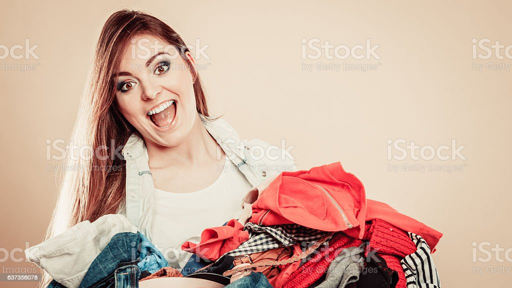Smiling girl hold pile of clothes. stock photo