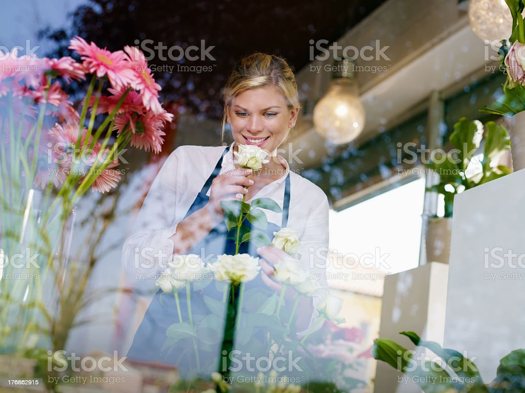Smiling girl holding a flower in the window of a flower shop royalty-free stock photo
