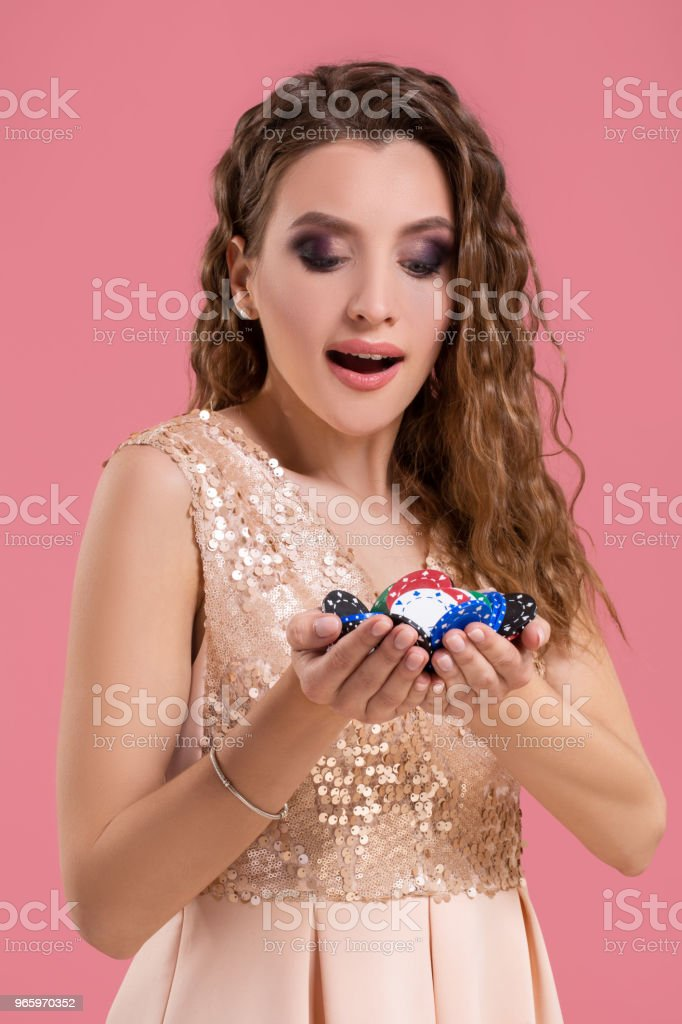 Smiling girl holding a gambling chips in her nands on pink background - Royalty-free Addiction Stock Photo
