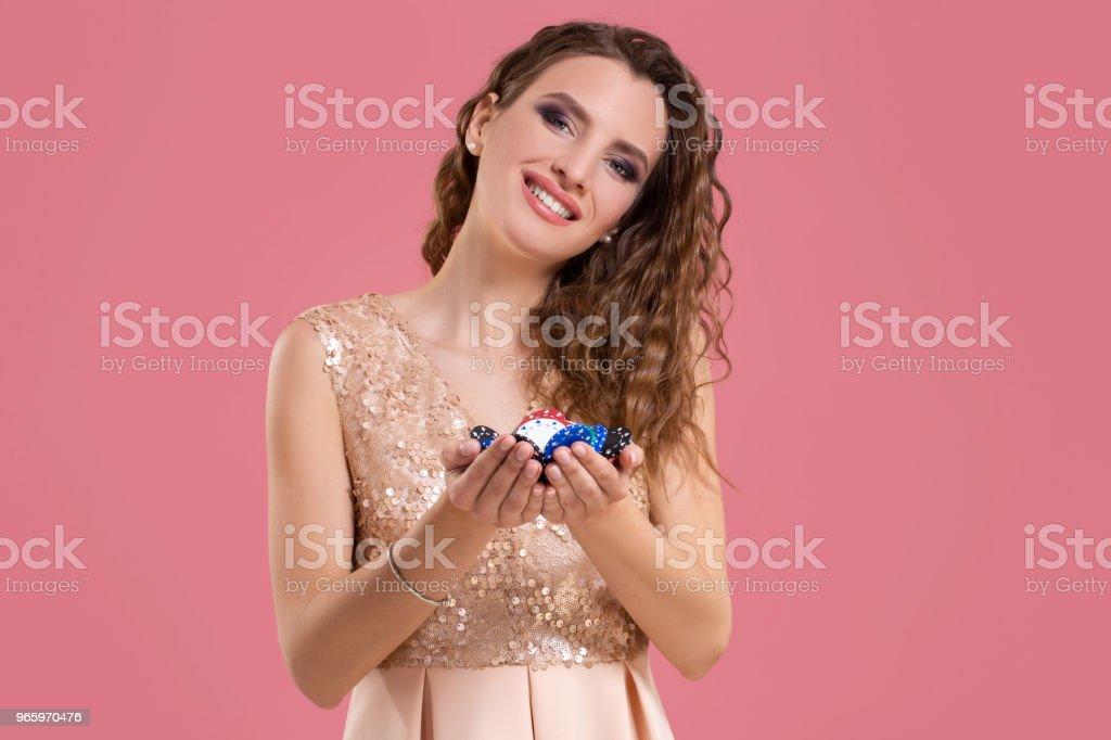 Lächelndes Mädchen hält ein Glücksspiel Chips in ihrem Nands auf rosa Hintergrund - Lizenzfrei Erfolg Stock-Foto
