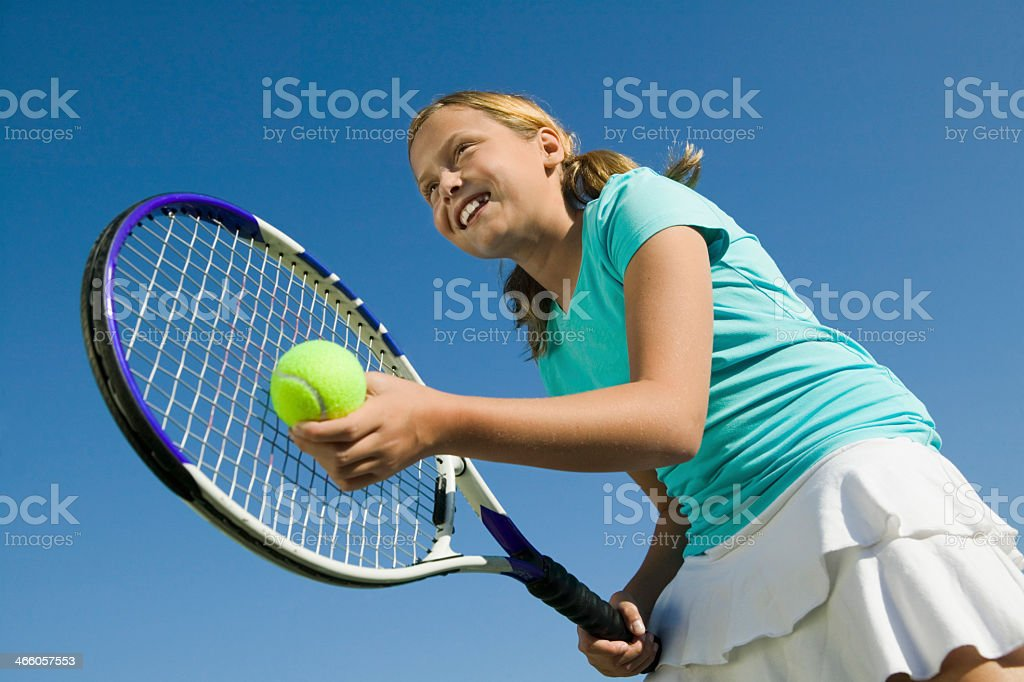 Smiling girl holding a tennis racket and ball stock photo