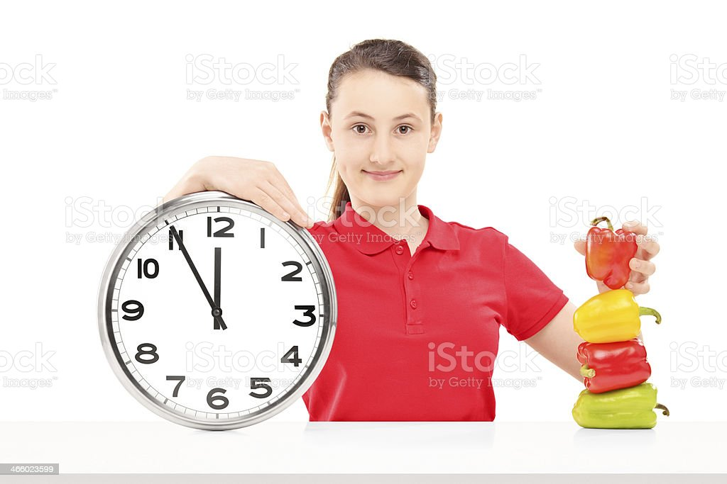 Smiling girl holding a wall clock and peppers on table royalty-free stock photo