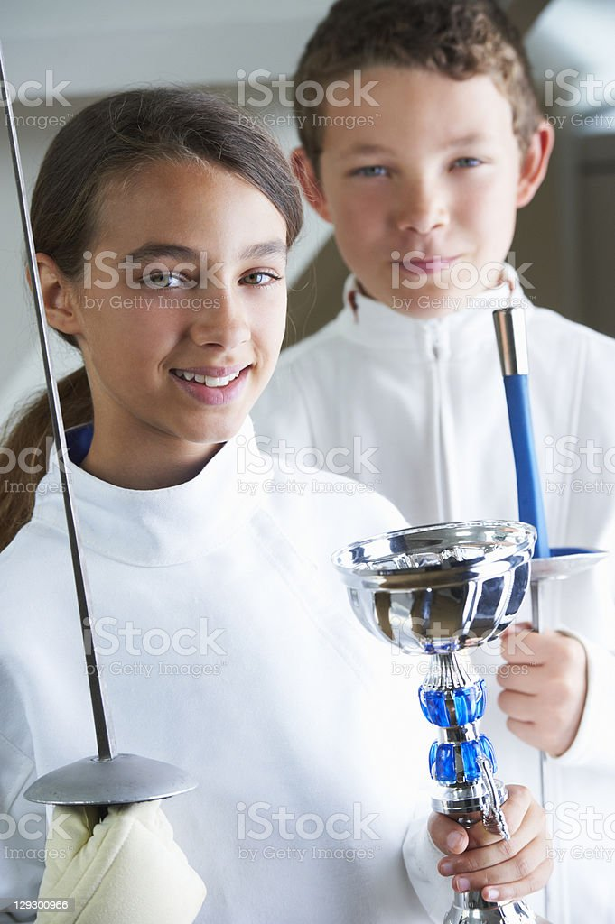 Smiling girl holding fencing trophy stock photo