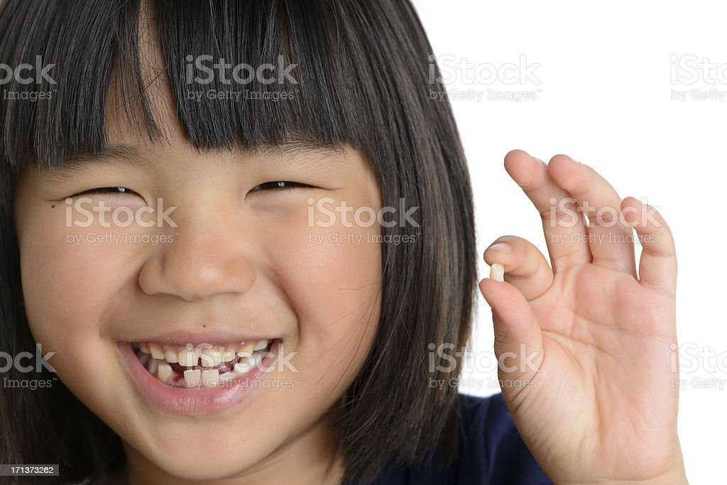 Smiling Girl Holding Missing Tooth stock photo