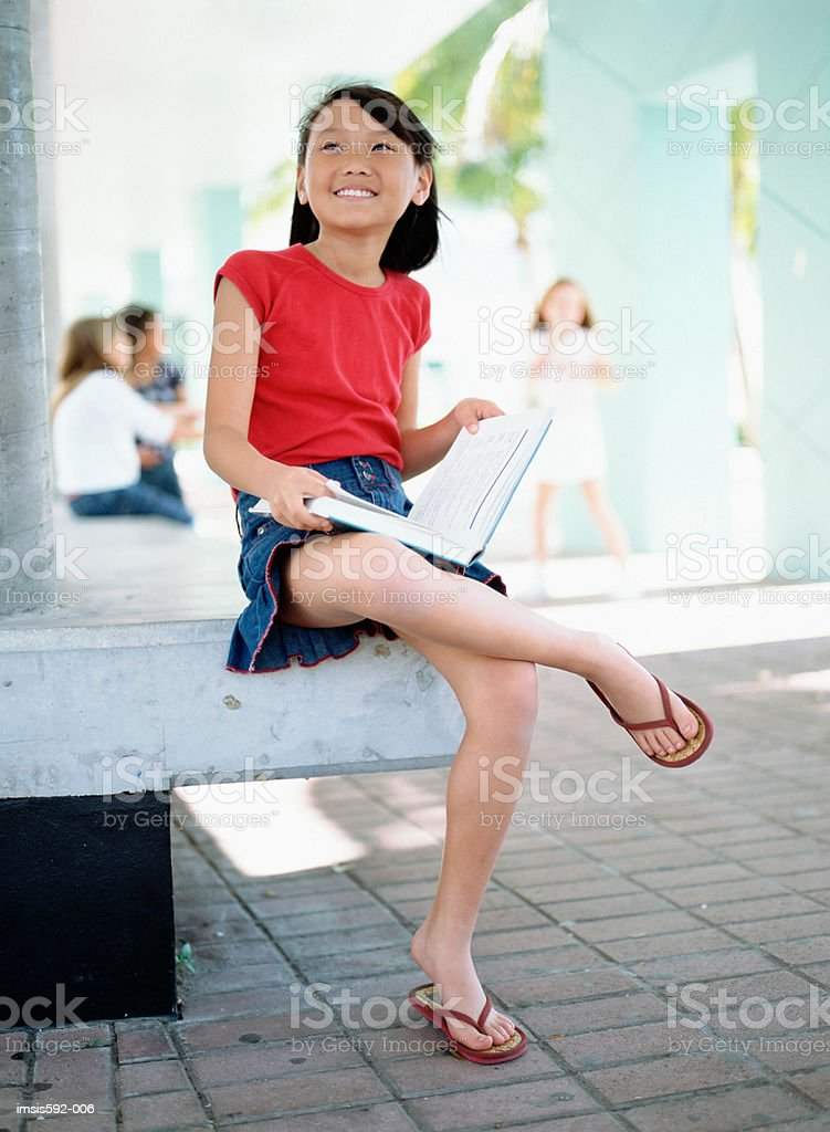 Smiling girl holding textbook royalty free stockfoto