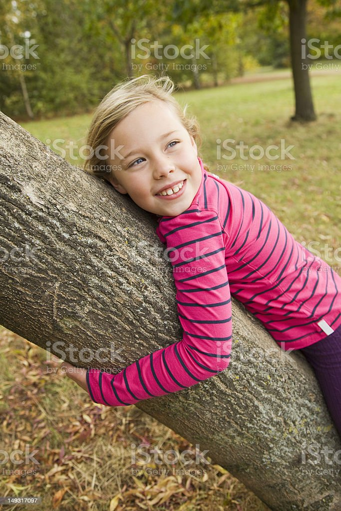 Smiling girl hugging tree outdoors royalty-free stock photo