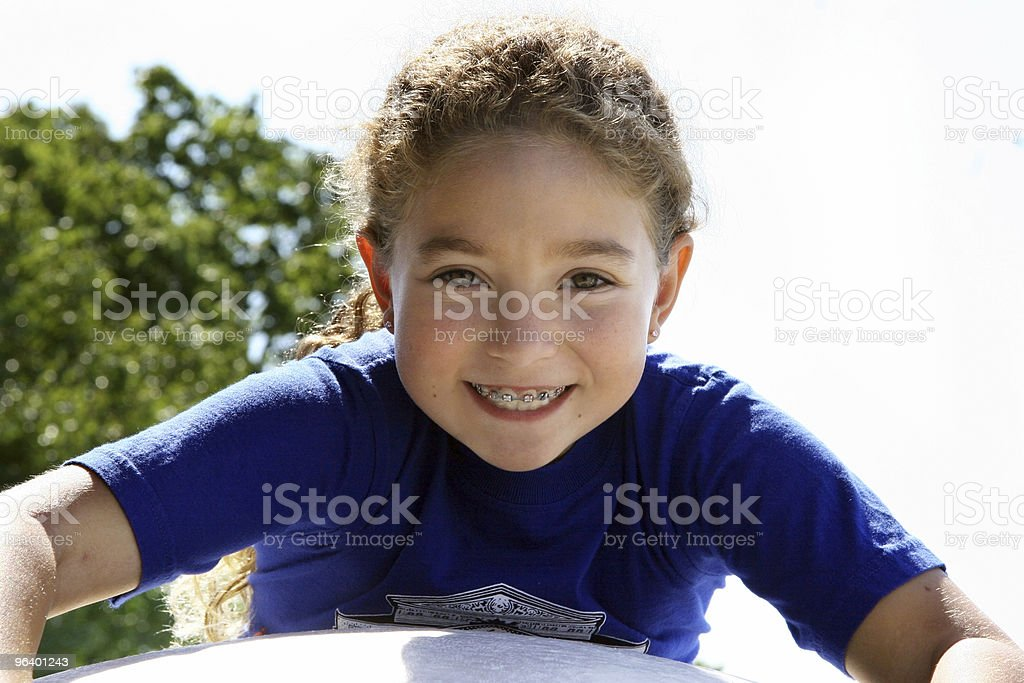 A smiling girl in a blue shirt seated at a table, outdoors - Royalty-free Adolescence Stock Photo
