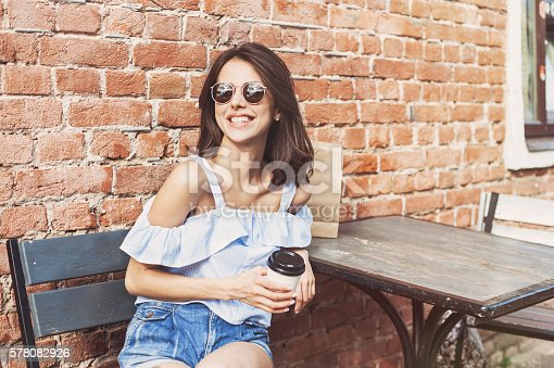 istock Smiling girl in a cafe outdoors 578082926