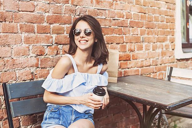 smiling girl in a cafe outdoors - gesichtertassen stock-fotos und bilder