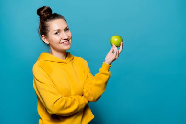 chica sonriente en una sudadera sostiene una manzana en la mano - foto de stock
