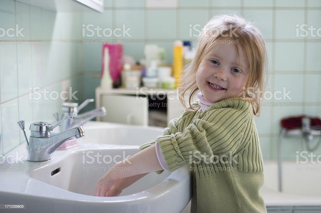 Smiling girl in bathroom, washing hands royalty-free stock photo