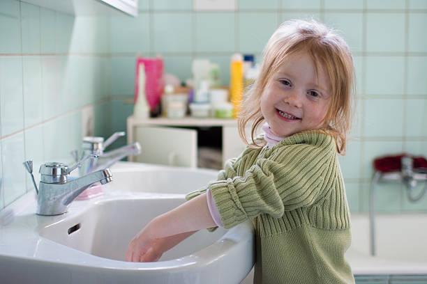lächelnd mädchen im badezimmer, hände waschen - hände wasser wasserhahn kinder lachen stock-fotos und bilder
