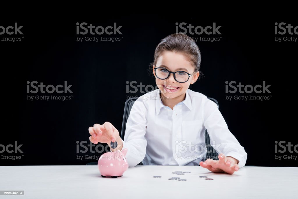 Smiling girl in formal wear putting coin into piggy bank foto stock royalty-free