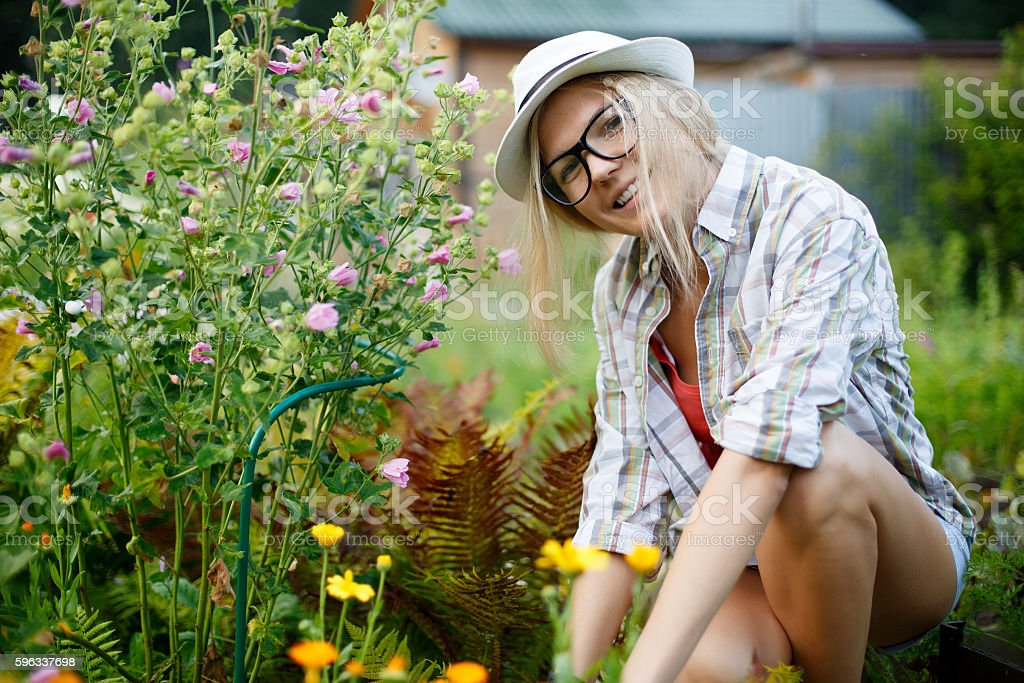smiling girl in glasses and hat sitting next flowers Lizenzfreies stock-foto