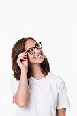 Smiling girl in glasses looking uyp, studio