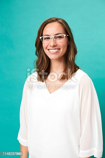 Smiling girl in glasses against blue