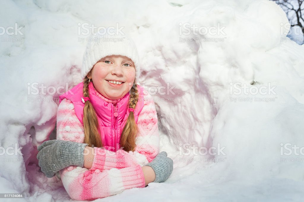Smiling girl in pink wear laying at the snow hole stock photo