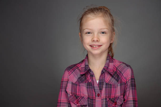 smiling girl in purple shirt looking straight at camera stock photo
