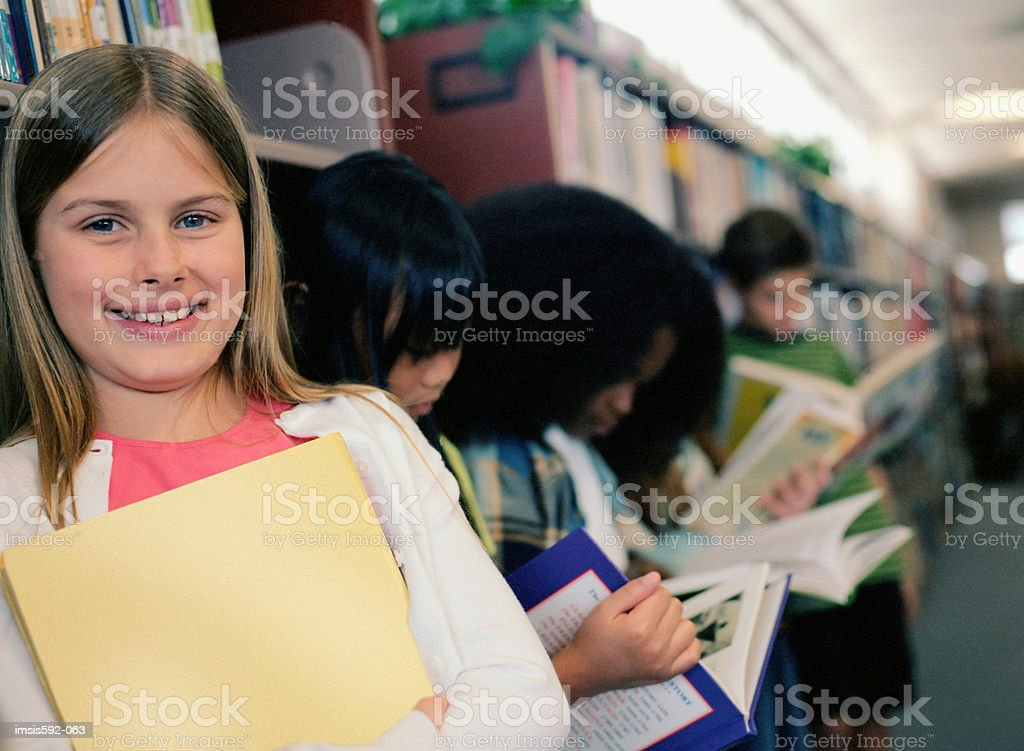 Smiling girl in school library royalty-free stock photo