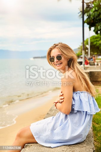 Smiling girl in shades and dress at beach