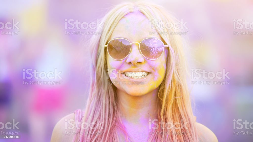 Smiling girl in sunglasses covered in colorful dyes, summer vacation,...