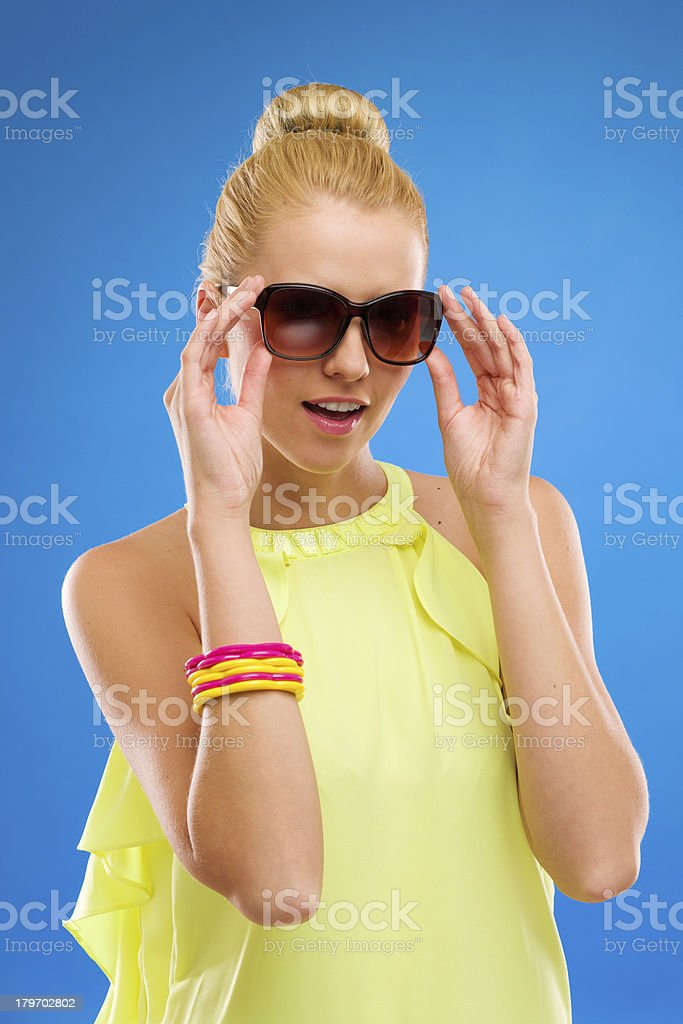 Smiling girl in sunglasses on blue background. royalty-free stock photo