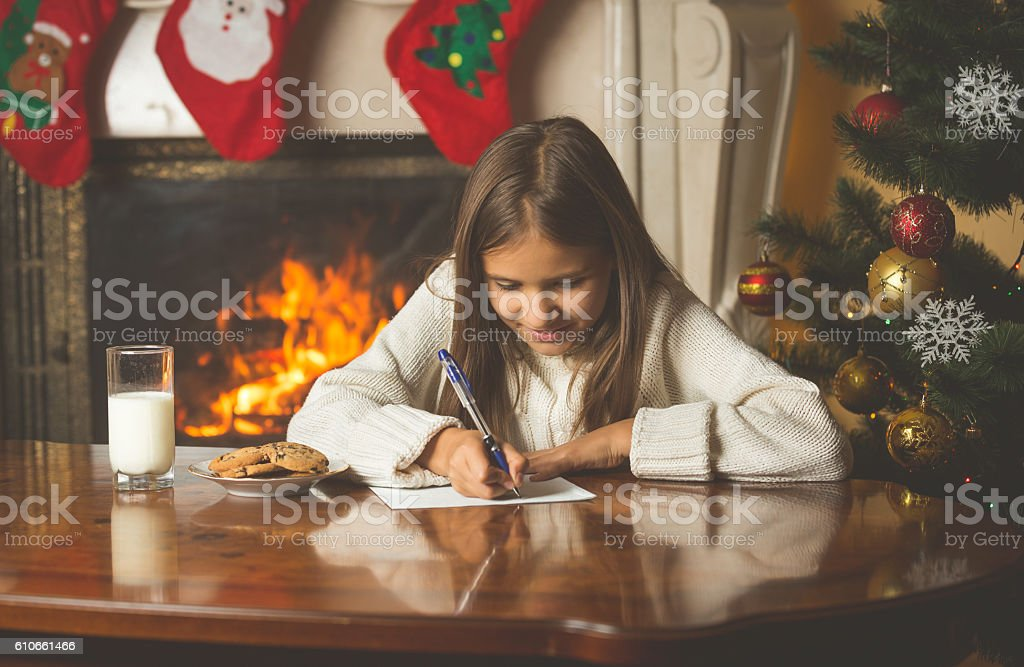Smiling girl in sweater sitting at fireplace and writing letter stock photo