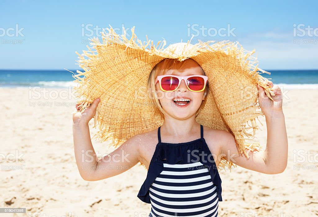 Smiling girl in swimsuit and straw hat on white beach stock photo