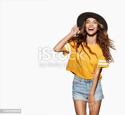 Young cute woman in stylish dark hat. Portrait of brunette model in trendy clothes posing at studio. Modern fashion concept. Isolated on white background