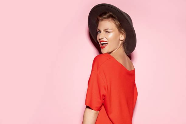 Smiling girl in trendy hat and red dress stock photo