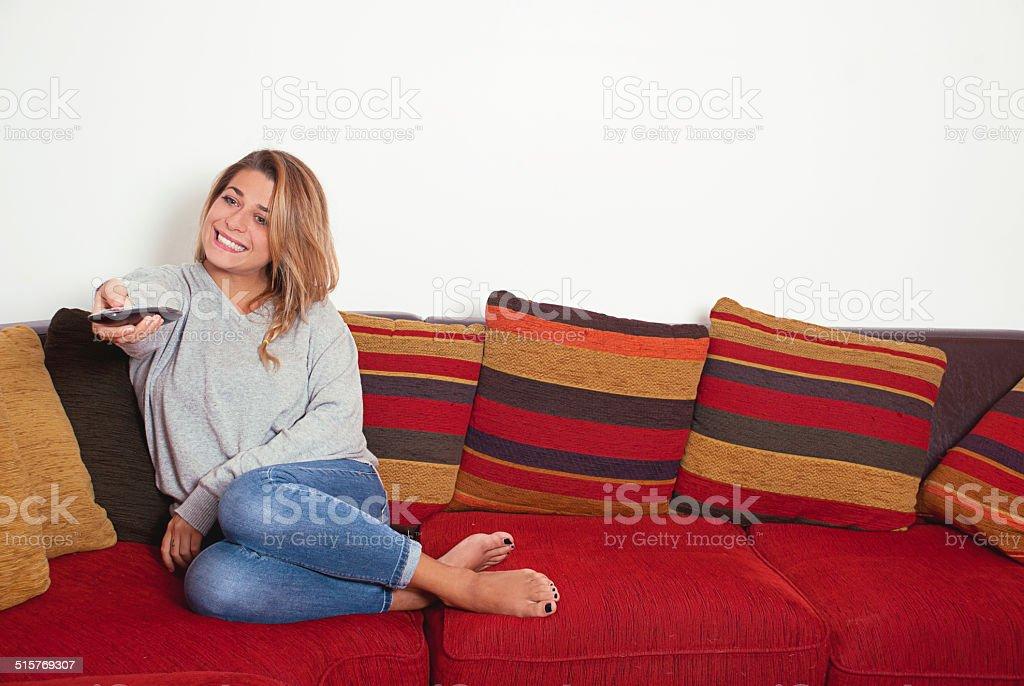 Lächelnd Mädchen ist vor dem Fernseher mit Fernbedienung – Foto