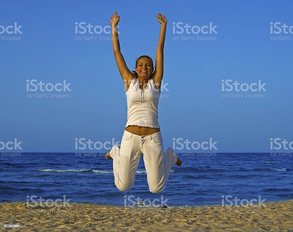 Smiling girl jump at the beach royalty-free stock photo