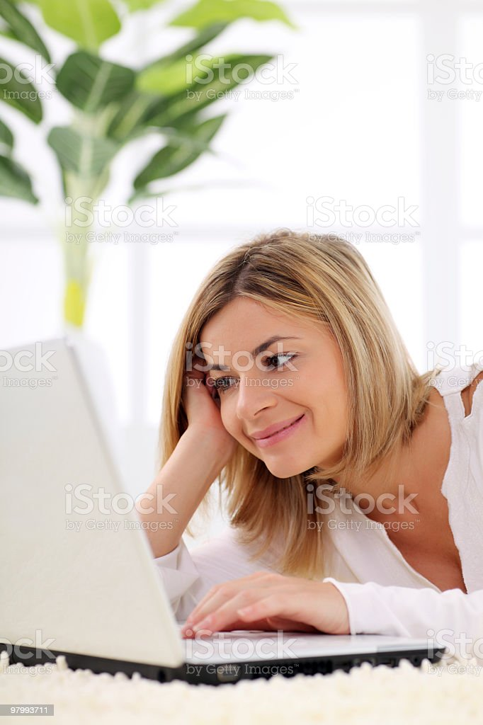 Smiling girl laying down on carpet with laptop royalty-free stock photo