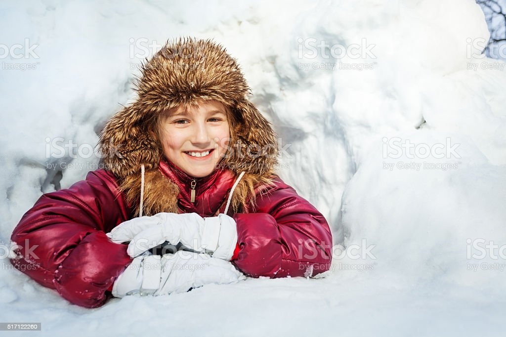 Smiling girl laying in the snow cave stock photo