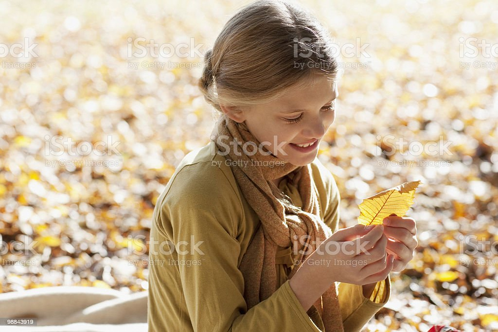 Smiling girl looking at autumn leaf outdoors royalty-free stock photo