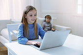 istock Smiling girl looking at the screen of a laptop 875554304