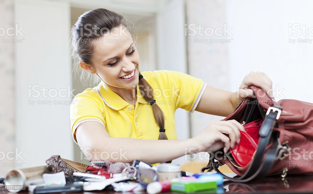 Smiling girl looking for something in handbag stock photo