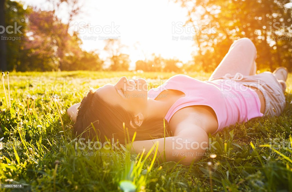 Smiling girl lying in grass and enjoying the sunset. stock photo
