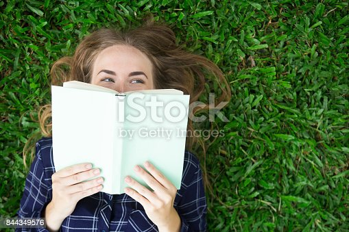 862602714 istock photo Smiling Girl Lying on Grass and Hiding Behind Book 844349576