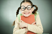 Cute girl wearing big black glasses is looking at the camera and smiling.  She is holding her book tightly. Gray background.
