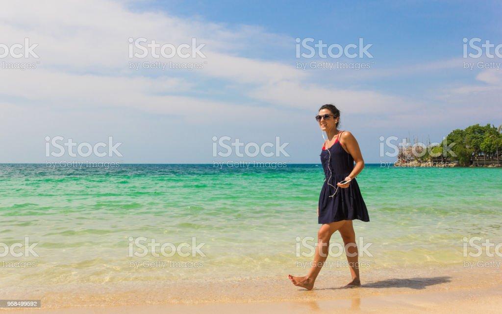 fb9f35969 Niña sonriente en vestido azul escuchando música mientras caminaba por la  orilla foto de stock libre